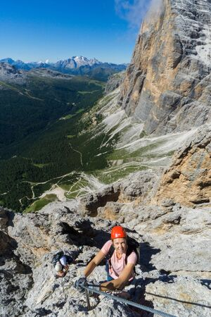 two young mountain climbers on very exposed Via Ferrata in Alta Badia in the Italian Dolomites