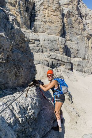attractive brunette female mountain climber on an exposed Via Ferrata in the South Tyrol having fun and smiling
