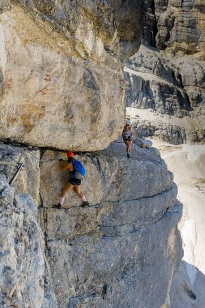 two female mountain climbers on very exposed Via Ferrata in Alta Badia in the Italian Dolomites
