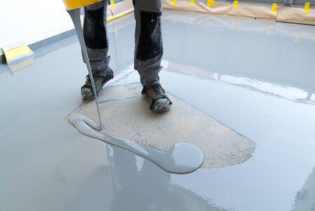 Un trabajador de la construcción renueva el piso del balcón y vierte resina hermética y pegamento antes de picar y sellar Foto de archivo