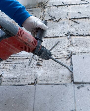 detail view of a construction worker using a handheld demolition hammer and wall breaker to chip away and remove old floor tiles during renovation work Фото со стока - 130070891