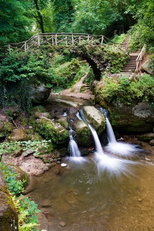 the picturesque Schiessentuempel waterfall in lush green summer forest in Luxembourg with an old bridge above