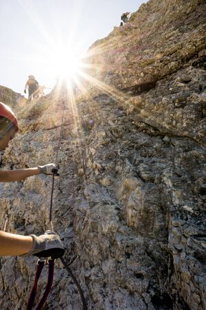 group of mountain climbers on a vertical Via Ferrata in the Italian Dolomites with a sun star shining in bright golden light Reklamní fotografie