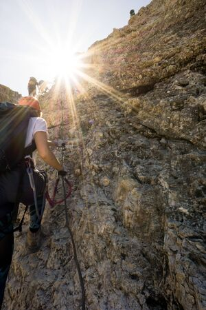 group of mountain climbers on a vertical Via Ferrata in the Italian Dolomites with a sun star shining in bright golden light Reklamní fotografie - 130070789