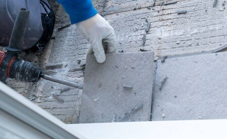 detail view of a construction worker using a handheld demolition hammer and wall breaker to chip away and remove old floor tiles during renovation work Фото со стока - 130070735