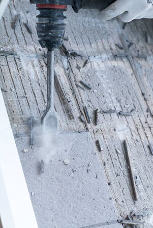 detail view of a construction worker using a handheld demolition hammer and wall breaker to chip away and remove old floor tiles during renovation work Фото со стока - 130070736
