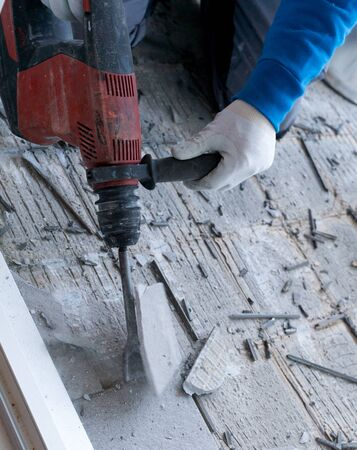 detail view of a construction worker using a handheld demolition hammer and wall breaker to chip away and remove old floor tiles during renovation work Фото со стока - 130070739