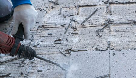 detail view of a construction worker using a handheld demolition hammer and wall breaker to chip away and remove old floor tiles during renovation work Фото со стока - 130070740