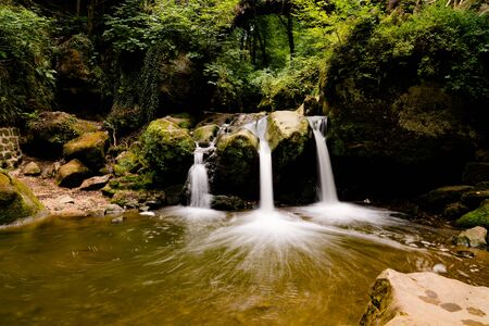 the picturesque Schiessentuempel waterfall in lush green summer forest in Luxembourg Stok Fotoğraf