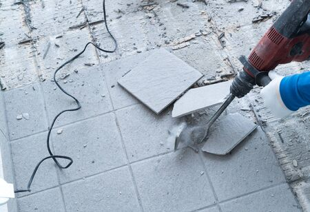 detail view of a construction worker using a handheld demolition hammer and wall breaker to chip away and remove old floor tiles during renovation work Фото со стока - 130070752