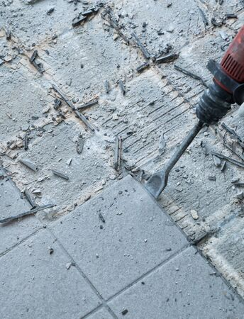 detail view of a construction worker using a handheld demolition hammer and wall breaker to chip away and remove old floor tiles during renovation work Фото со стока - 130070704