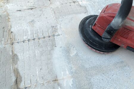 A construction worker uses a power concrete grinder for removing tile glue and resin during renovation work