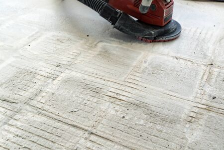 A construction worker uses a power concrete grinder for removing tile glue and resin during renovation work Archivio Fotografico
