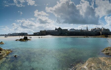 Saint Malo, Brittany  France - 19 August 2019: panorama view of the historic old town of Saint-Malo with beach and coast at low tide and tourists enjoying the summer day