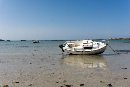 horizontal view of boats stranded in shallow water and sand on a deserted idyllic beach at low tide