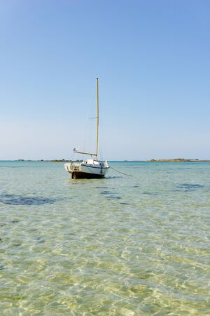 vertical ocean coast and beach landscape with small sailboat under a blue sky at low tide Stock fotó