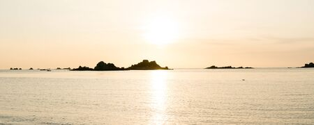 View of a sunset over a calm ocean with rocks and reefs in silhouette Stock fotó