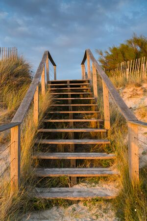 Romantic view of wooden stairs leading over sand dunes to the beach at sunset with reeds and grasses