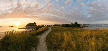 Panorama of idyllic coast and beach at sunset with sandy footpath leading into the distance