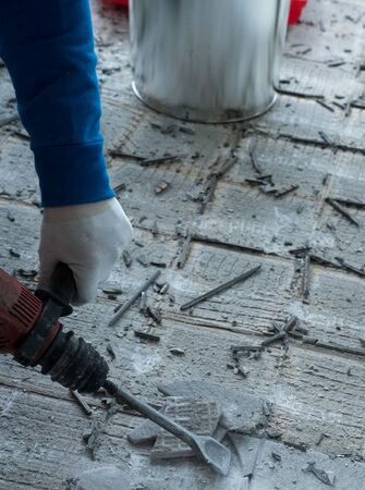 detail view of a construction worker using a handheld demolition hammer and wall breaker to chip away and remove old floor tiles during renovation work