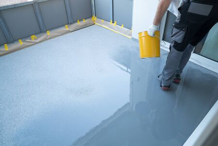 A construction worker renovates balcony floor and spreads chip floor covering on resin and glue coating before applaying water sealant Stockfoto