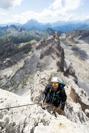 young handsome male climber on a steep and exposed rock face climbs a Via Ferrata in Alta Badia in the South Tyrol Imagens