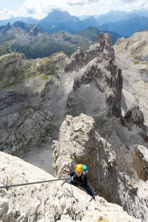 Vertical view of an attractive female climber on a steep Via Ferrata in the Italian Dolomites with a great view behind Imagens