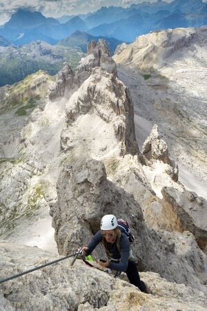Vertical view of a cool young attractive mountain climber checks her mobile phone while climbing a Via Ferrata in the Dolomites Imagens