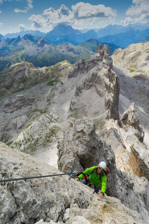 handsome male climber on a steep and exposed rock face climbs a Via Ferrata in Alta Badia in the South Tyrol