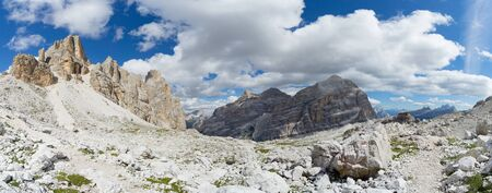 panorama view of wild mountain landscape with rocky peaks and a hiking trail marker and path in the foreground in the Italian Dolomites Imagens