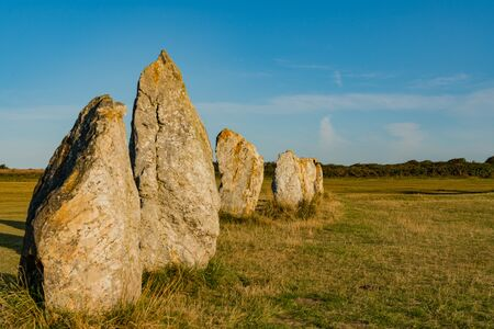 view of prehistoric monolith stone alignments in Brittany in warm morning light with the sun shining brightly