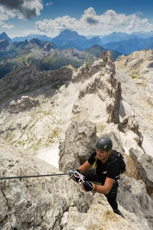 Vertical view of an attractive blonde female climber on a steep Via Ferrata in the Italian Dolomites with a great view behind