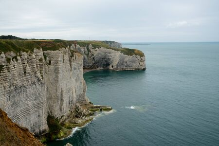 A view of the ocean and wild coast with green fields and jagged cliffs Imagens