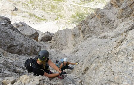 attractive women mountain climbers on a vertical and exposed rock face climbing a Via Ferrata in the Italian Dolomites