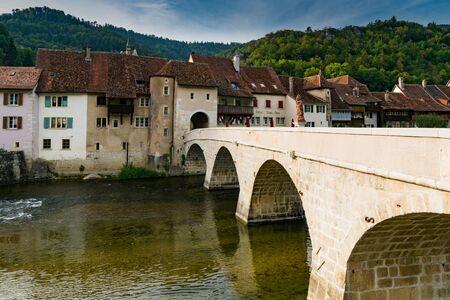 Saint-Ursanne, Jura  Switzerland - 27 August 2019: historic stone bridge leads to the gate and picturesque village of Saint-Ursanne