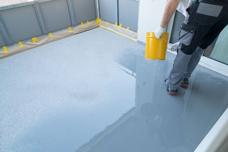 A construction worker renovates balcony floor and spreads chip floor covering on resin and glue coating before applying water sealant Imagens