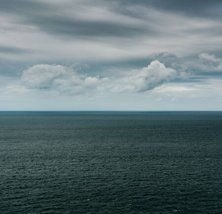 Square format view of empty ocean and sky landscape with expressive clouds