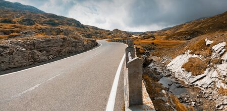 A two-lane road leading over a high remote and wild mountain pass in the Swiss Alps in autumn