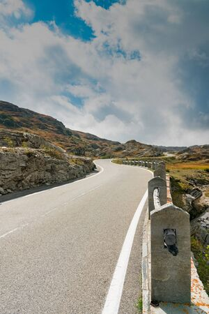 A vertical view of a two-lane road leading over a high remote and wild mountain pass in the Swiss Alps