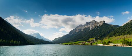 panorama view of an idyllic and picturesque turquoise mountain lake surrounded by green forest and mountain peaks in the Swiss Alps near Sufers