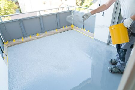 A construction worker renovates balcony floor and spreads chip floor covering on resin and glue coating before applying water sealant Stock Photo