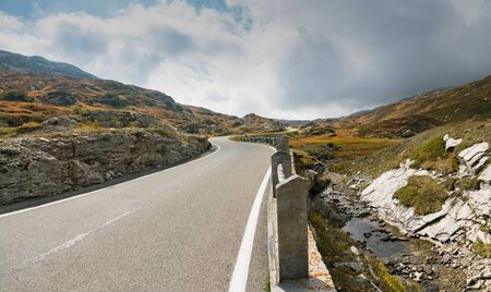 A two-lane road leading over a high remote and wild mountain pass in the Swiss Alps Imagens