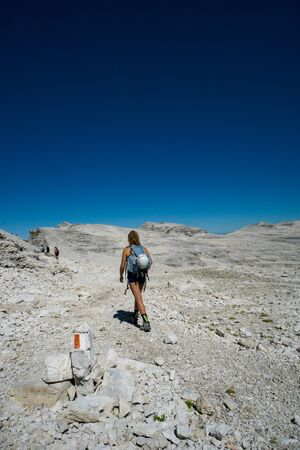 female mountain climber hikes across a wild rock desert high mountain plateau in the Dolomites after a hard climb