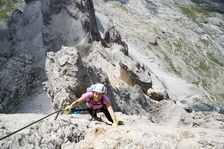 Horizontal view of attractive brunette female climber on a steep and exposed Via Ferrata in the Dolomites Imagens