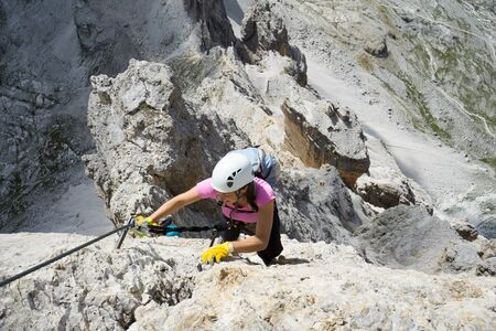Horizontal view of attractive brunette female climber on a steep and exposed Via Ferrata in the Dolomites Stock fotó