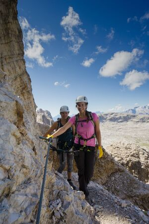 Vertical view of an attractive female climbers and twins on a steep Via Ferrata in the Italian Dolomites with a great view behind