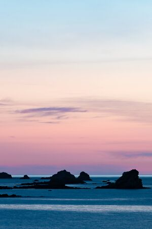 Vertical view of a sunset at the beach with a calm ocean and rocks and reefs under a lilac purple sky Stock fotó