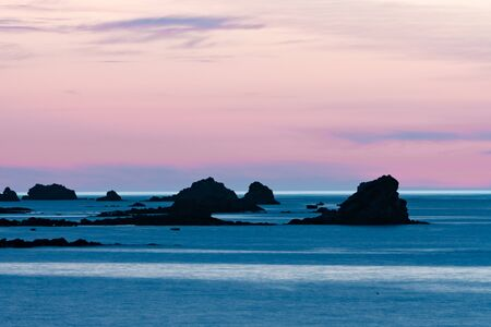 Horizontal view of a sunset at the beach with a calm ocean and rocks and reefs under a lilac purple sky Stock fotó