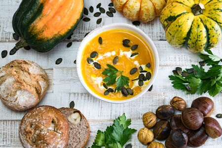 Top down view of organic pumpkin soup in a white bowl framed by chestnuts pumpkins parsley and chestnut bread and pumpkin seeds