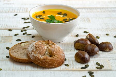 low angle view of organic pumpkin soup in a white bowl framed by chestnuts and chestnut bread and pumpkin seeds